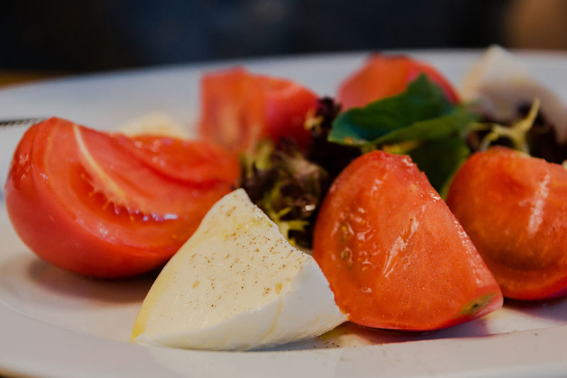 Caprese salad with mozzarella cheese tomatoes and herbs Food And Drink Food Freshness Healthy Eating Fruit Wellbeing Still Life Plate Indoors  Close-up Vegetable Tomato Ready-to-eat No People Table Red Focus On Foreground Selective Focus SLICE Serving Size Temptation