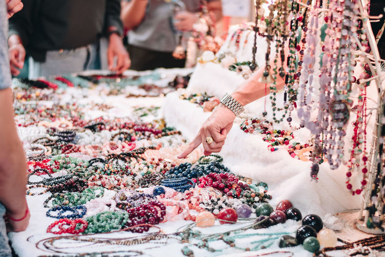 Person pointing at jewelries in market
