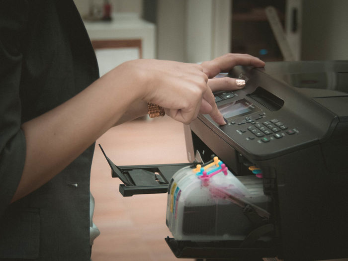 Midsection of woman using computer printer