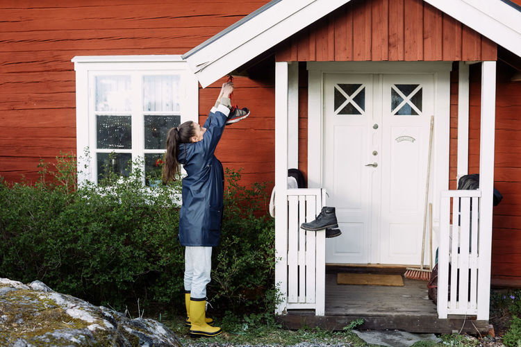 Full length of man standing outside house against building