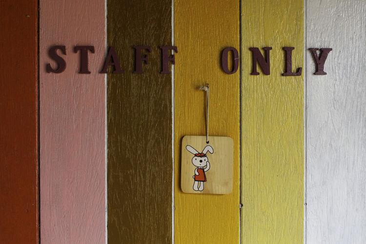 Close-up of restroom sign on wooden door