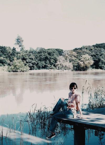 Man sitting by swimming pool against lake