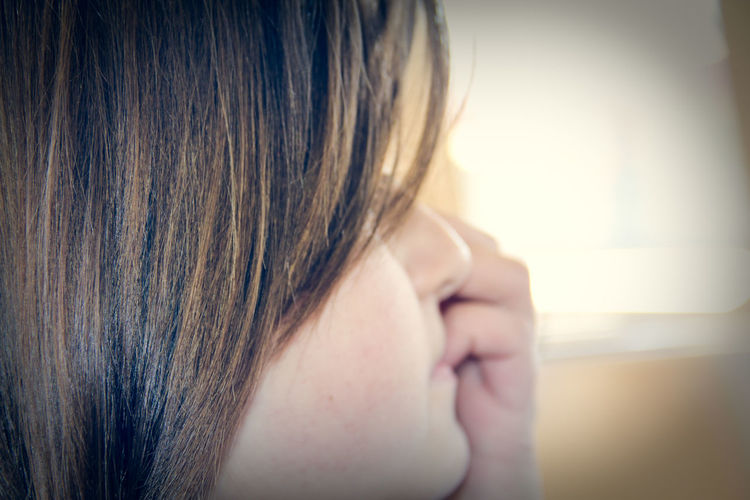 Close-Up Of Young Woman Looking Away While Sitting In Train