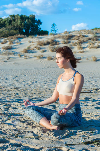 Young Woman Doing Yoga At Beach Against Sky