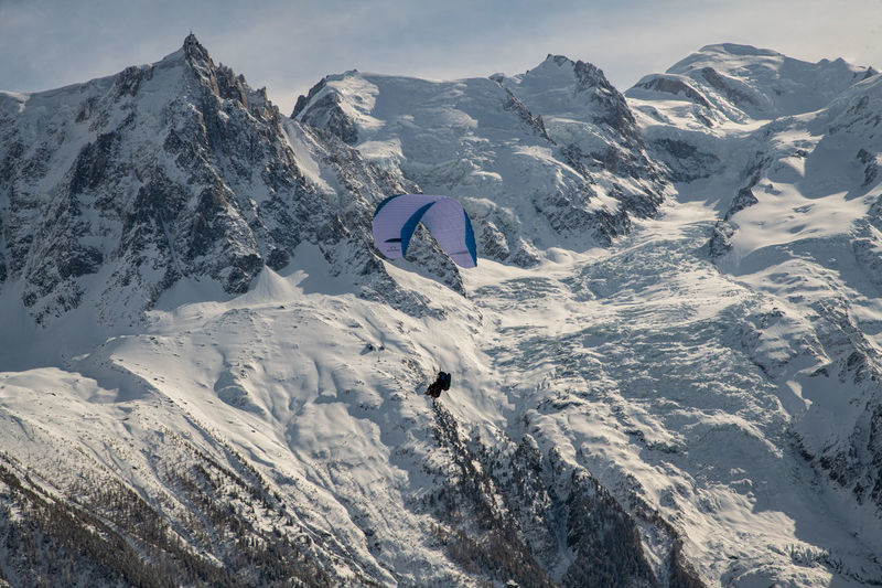 Person paragliding over snow covered mountains against sky