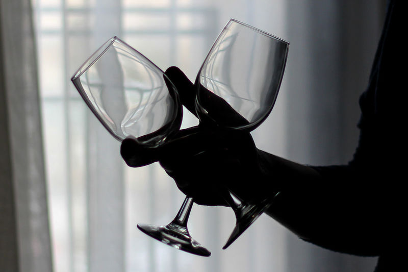 Cropped image of silhouette person holding wineglasses