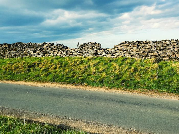 Empty road by stone wall against sky