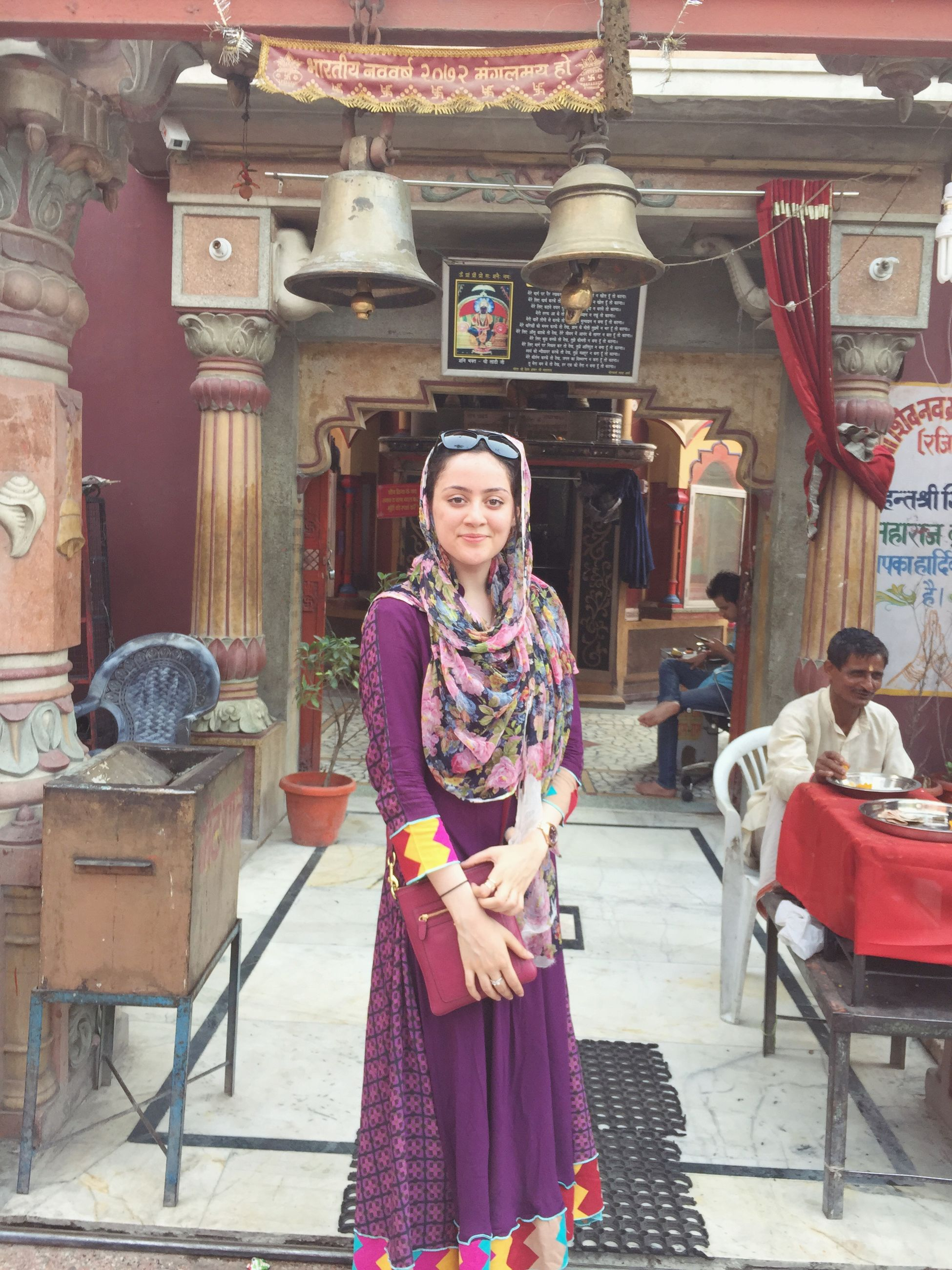 casual clothing, looking at camera, lifestyles, portrait, front view, person, standing, leisure activity, smiling, three quarter length, young adult, happiness, waist up, sitting, red, built structure, traditional clothing