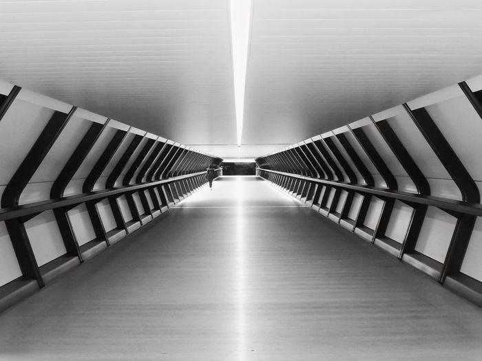 Rear view of woman walking on illuminated corridor