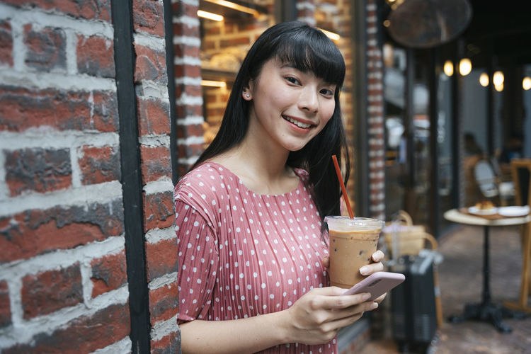 Portrait of smiling young woman holding ice cream outdoors