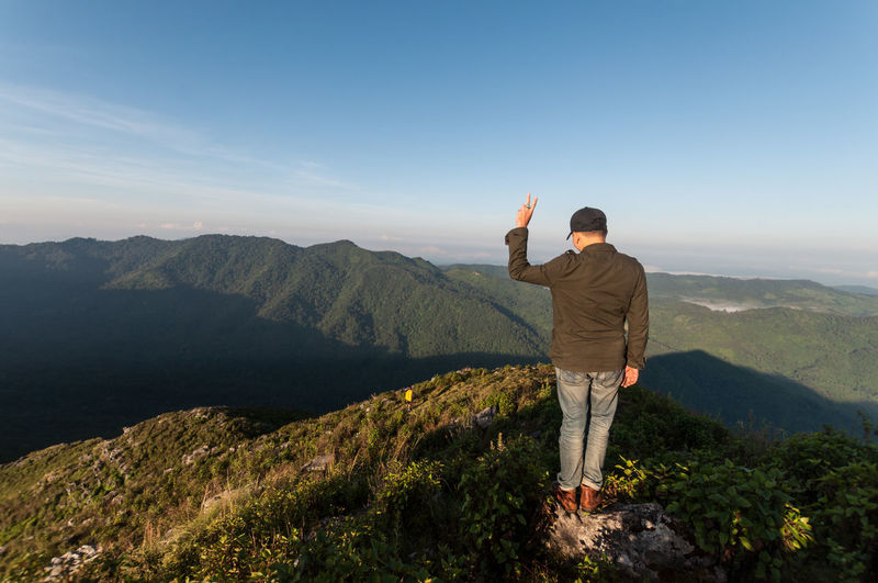 Rear view of man gesturing while standing on mountain against sky