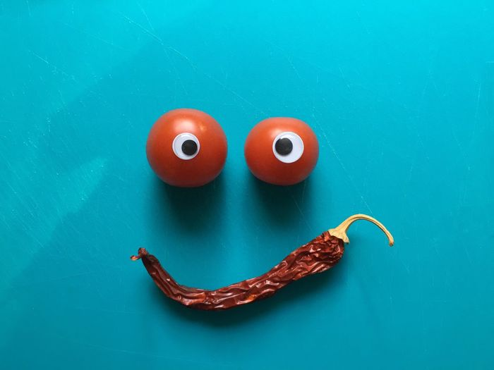Anthropomorphic smiley face made from vegetable on turquoise table