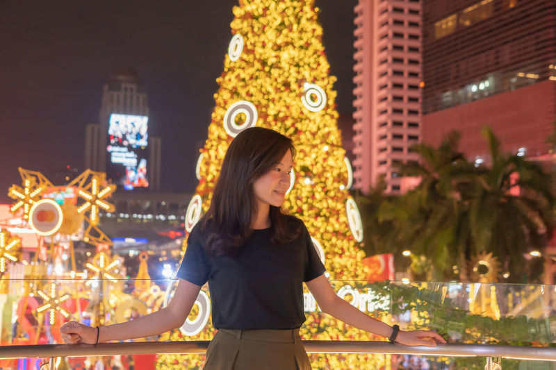 Smiling woman standing against illuminated christmas tree in city at night