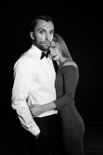Portrait of elegant couple standing against black background