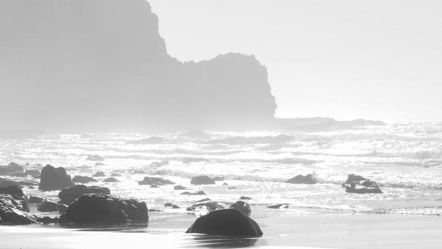 Silhouette rocks on shore against sky