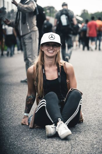 One Person Sitting Lifestyles Full Length Portrait Leisure Activity Casual Clothing Young Women Real People Front View Fashion Adult Hat Young Adult Hairstyle City Glasses Smiling Cap