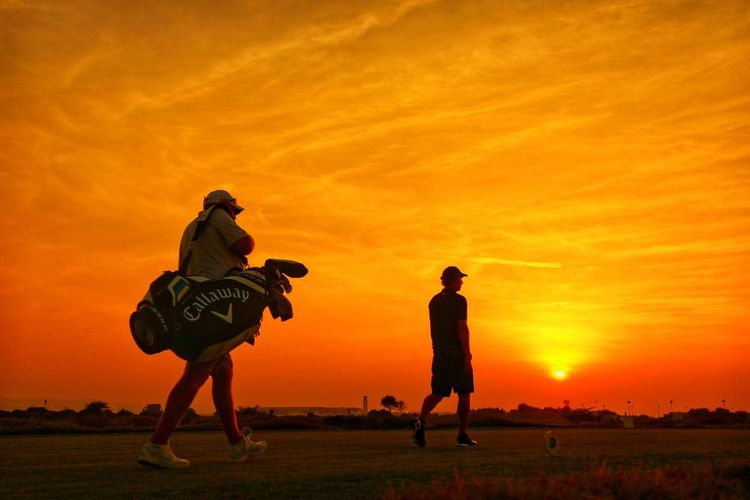 Golf at Sunset..... Golf Course Beauty Golf Course Golf Sunset Orange Color Real People Sky Leisure Activity Togetherness Full Length Silhouette Nature Men Outdoors Sport People Friendship Lifestyles
