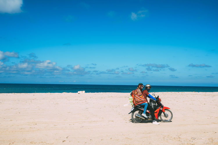 People riding motorcycle at beach against blue sky during sunny day