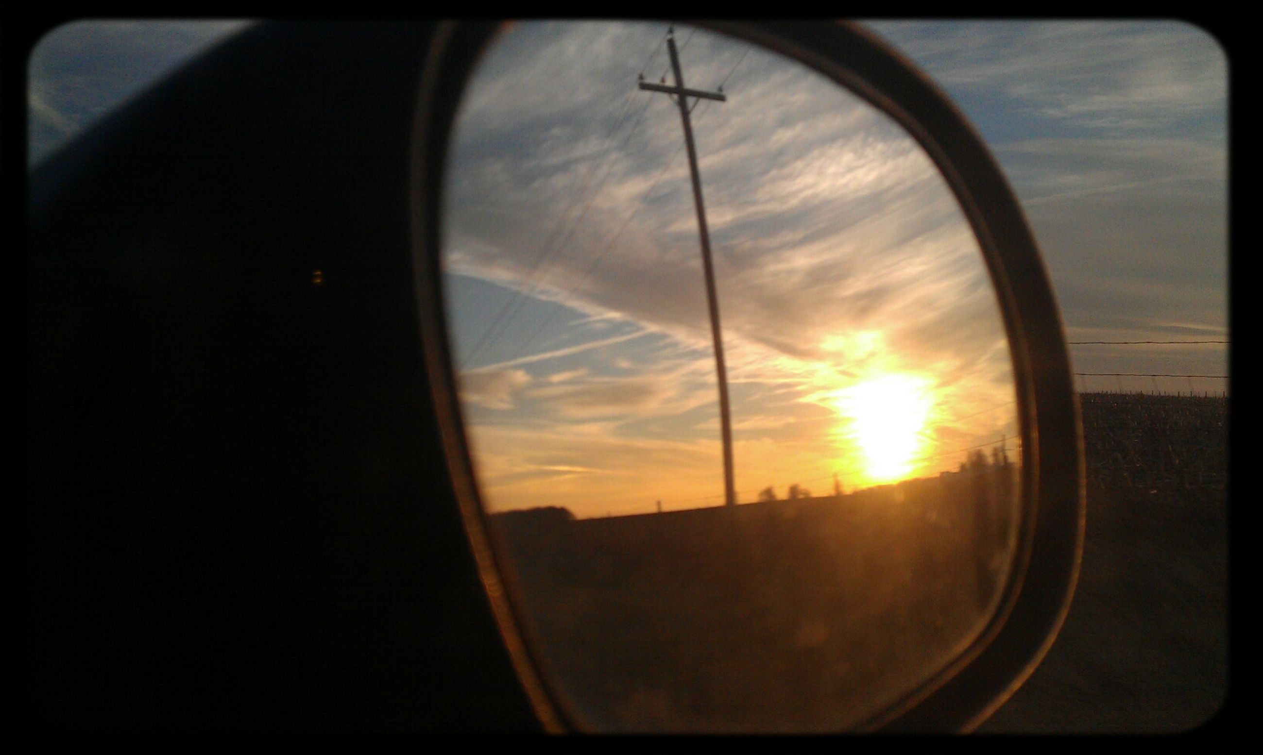 sunset, transportation, sun, sky, mode of transport, silhouette, orange color, vehicle interior, land vehicle, cloud - sky, car, glass - material, sunlight, reflection, transparent, window, side-view mirror, transfer print, travel, cloud