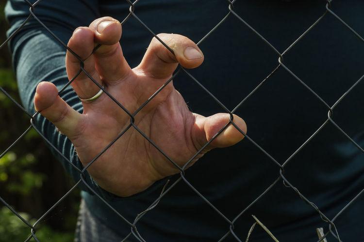 Male hand through a metal mesh
