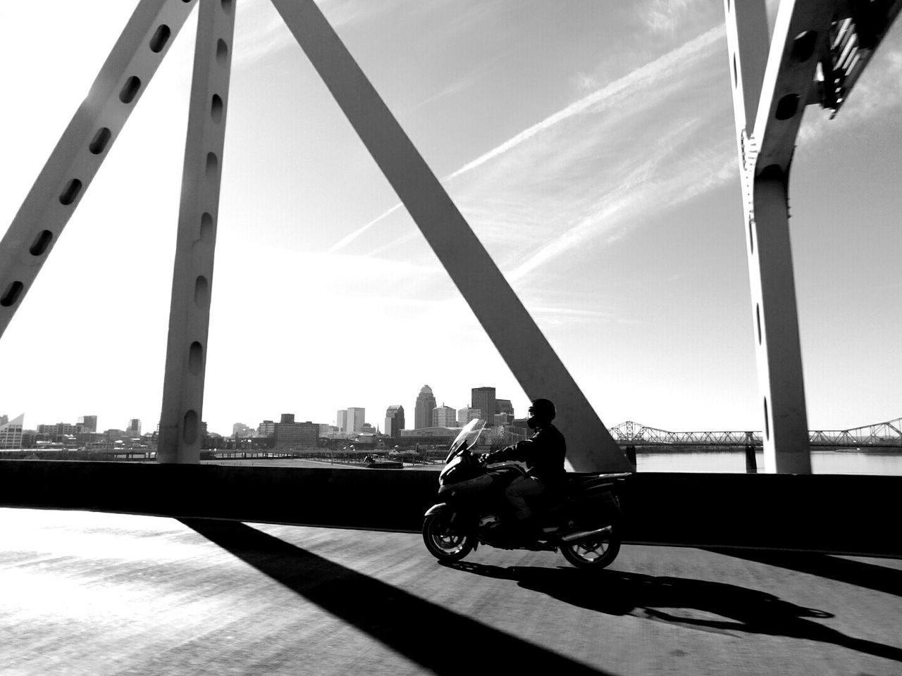 Man Riding Motorcycle On Bridge During Sunny Day