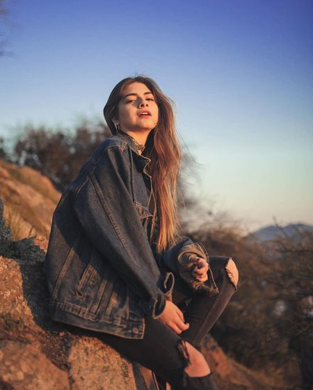Side view portrait of young woman wearing denim jacket while sitting on mountain during sunset
