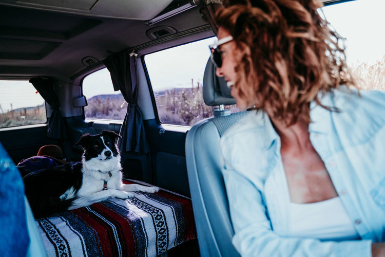 Woman looking at dog while sitting in camper trailer