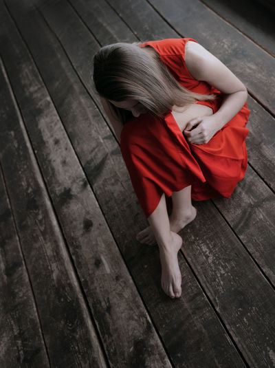 High angle view of woman sitting on wooden floor