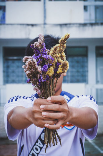 Midsection of person holding purple flowering plant