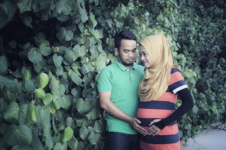 Husband touching stomach of pregnant wife while standing by plants
