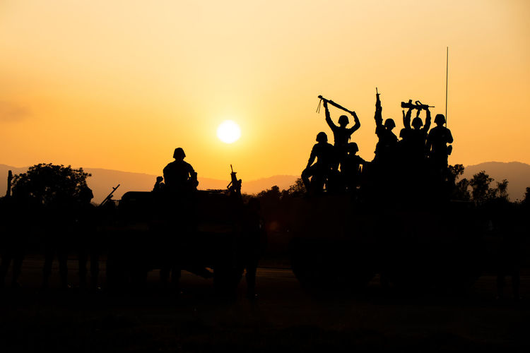 Silhouette Army Soldiers On Field Against Orange Sky