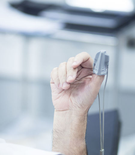 Cropped hand of patient wearing medical equipment in hospital