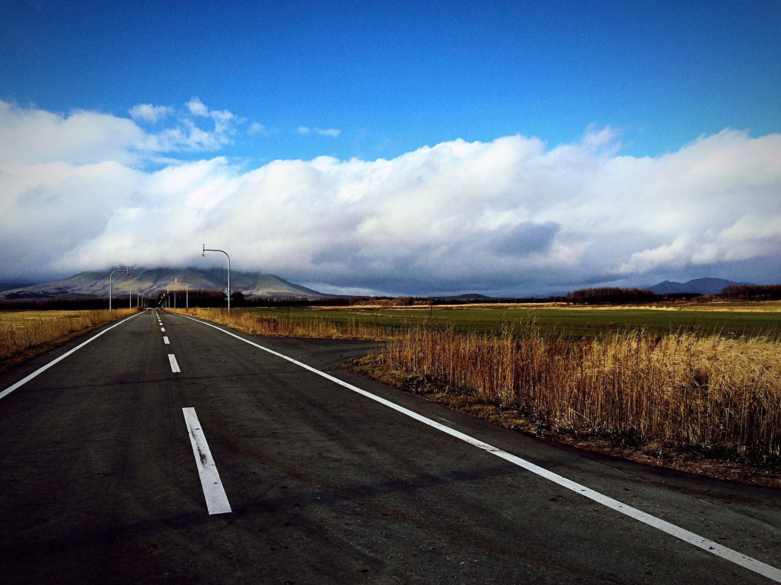 the way forward, transportation, road, sky, diminishing perspective, road marking, vanishing point, country road, landscape, cloud - sky, tranquil scene, empty road, empty, tranquility, cloud, asphalt, cloudy, scenics, nature, field
