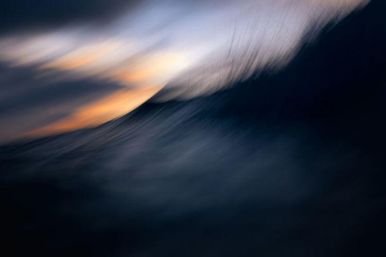 Defocused image of sea against sky at sunset