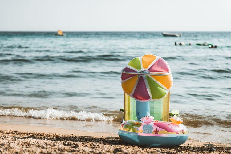 Toy on beach against sky