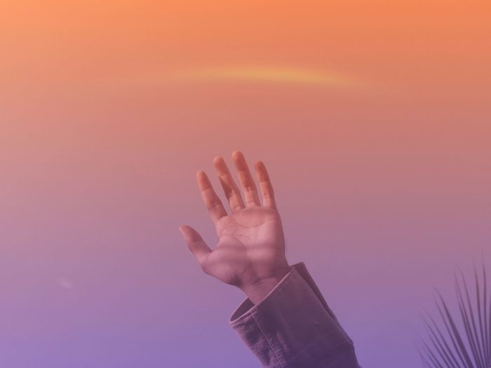 Close-up of person hand against sky during sunset