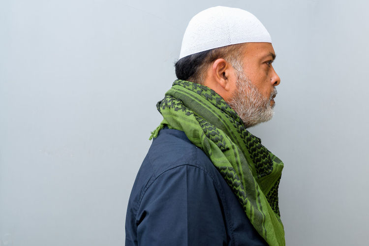 Side view of a man looking away over white background