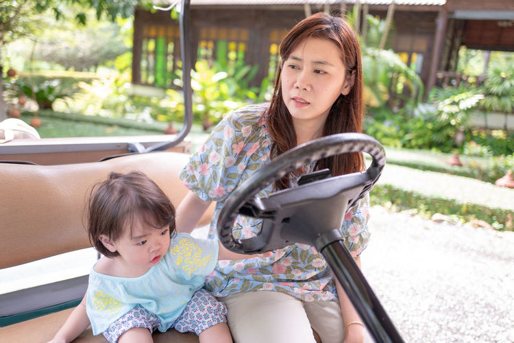 Woman Sitting With Daughter On Golf Cart