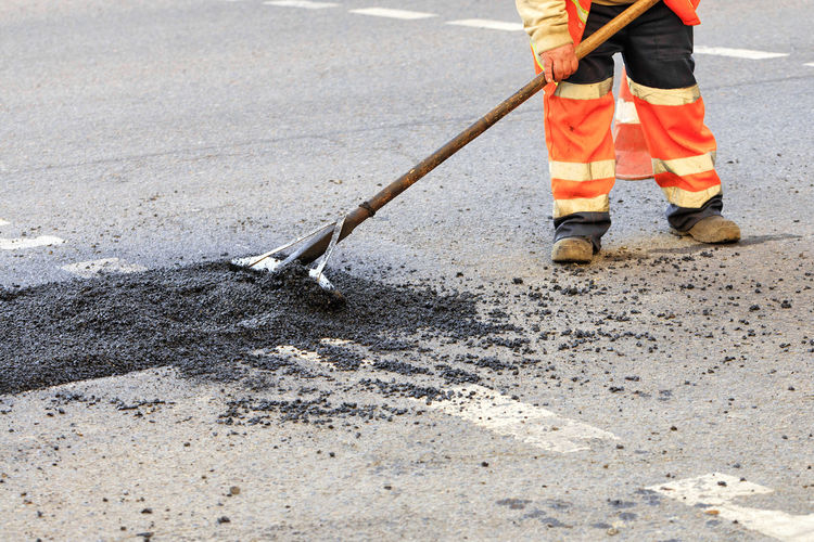 Low section of construction worker working on road