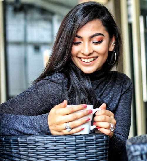 Smiling Young Woman Holding Coffee Cup In Cafe