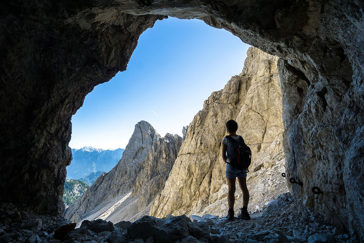 Rear View Of Woman With Backpack Standing In Cave By Mountains