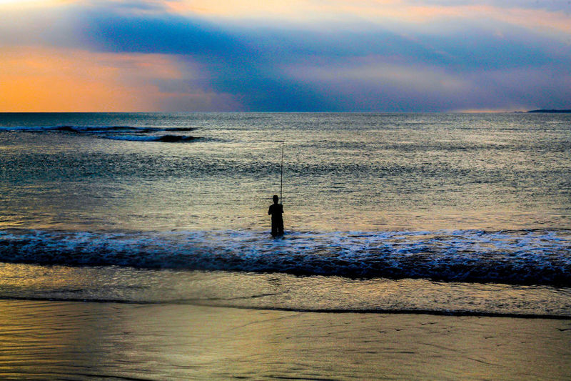 Fishing Ocean Fishing Water Sea Sunset Beach Standing Silhouette Sky Horizon Over Water Cloud - Sky Calm Wave Ocean Fisherman Fishing Rod Fishing Tackle Sandy Beach Sand Low Tide Tide