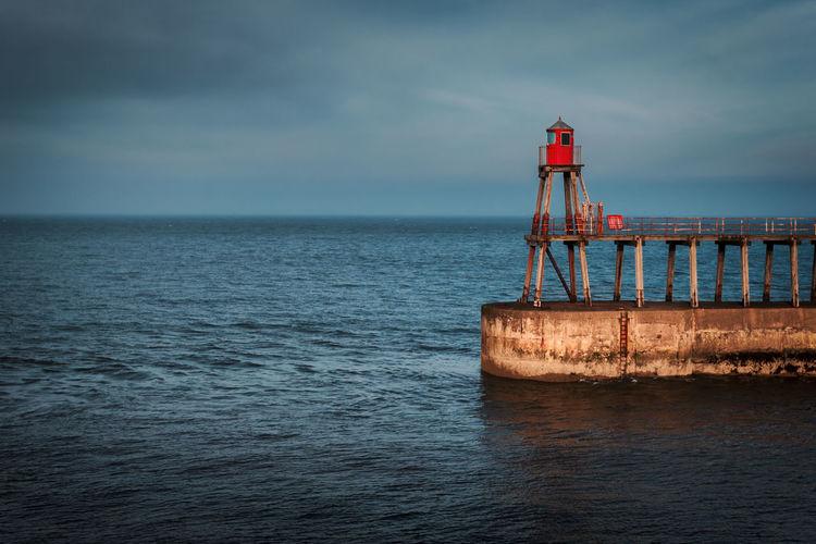 Lighthouse At Harbor On Sea Against Sky