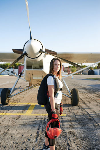 Portrait of woman standing by airplane against sky