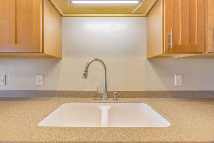 Sink in clean kitchen. Sink in clean kitchen. Located in a model home in Utah Valley. Absence Architecture Bathroom Domestic Kitchen Domestic Room Faucet Flooring Home Home Interior Home Showcase Interior Household Equipment Hygiene Indoors  Kitchen Kitchen Counter Kitchen Sink Luxury Modern No People Simplicity Sink