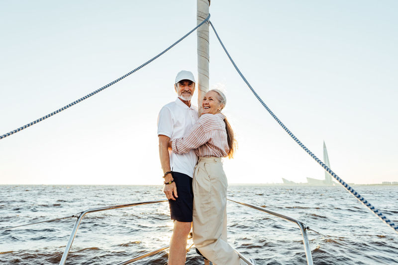 Smiling senior couple embracing in sailboat against sky