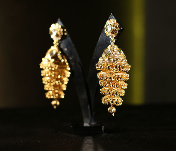 Close-up of gold earrings on table