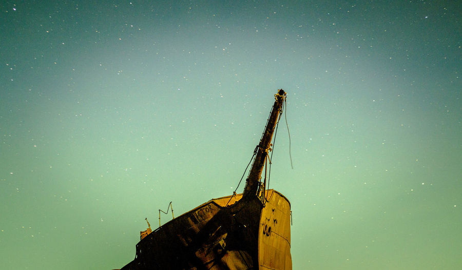 Low angle view of damaged ship against sky at night