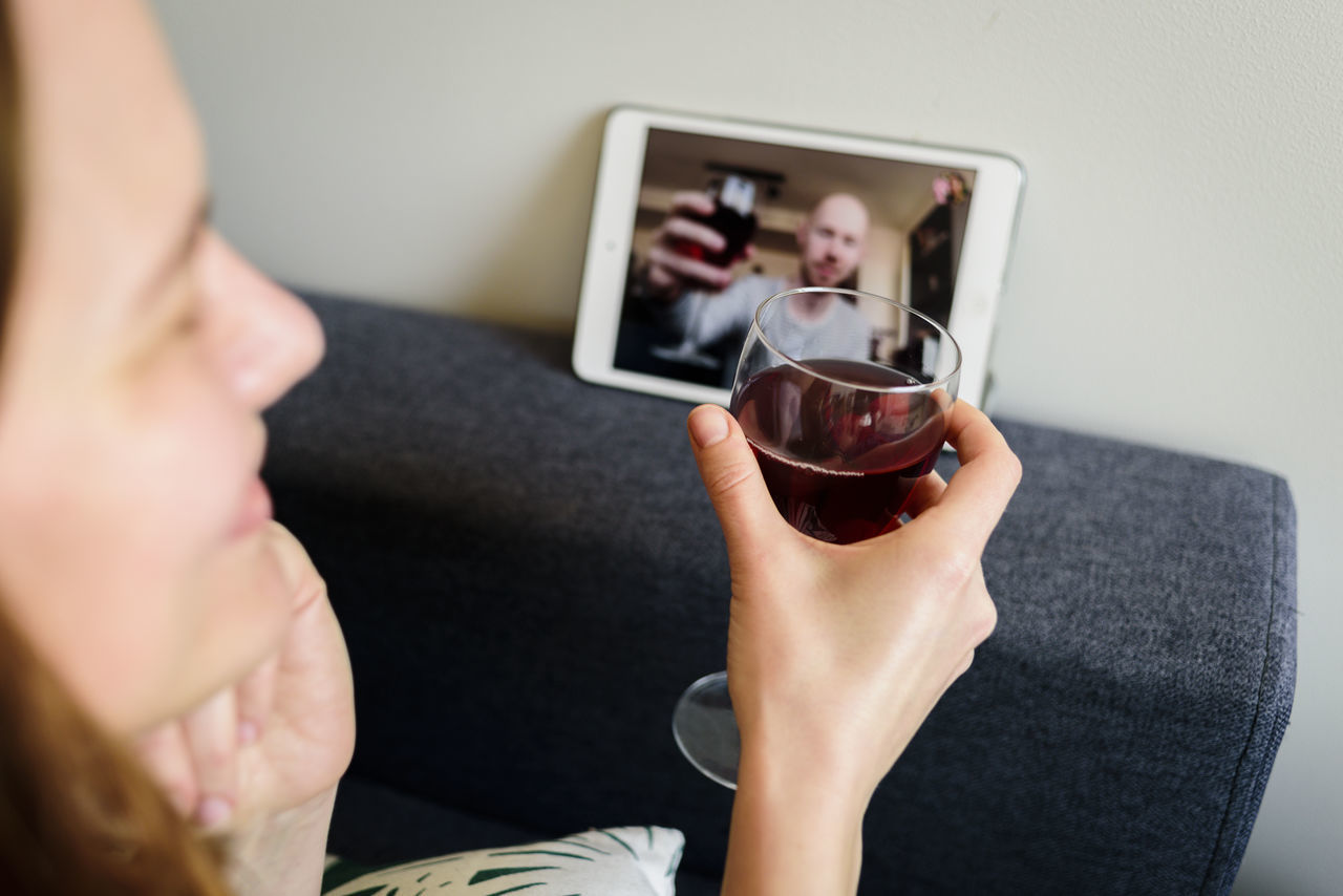 Woman toasting wineglass while doing video conference on digital tablet at home