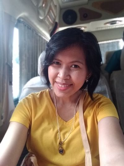 Portrait of smiling woman sitting in bus